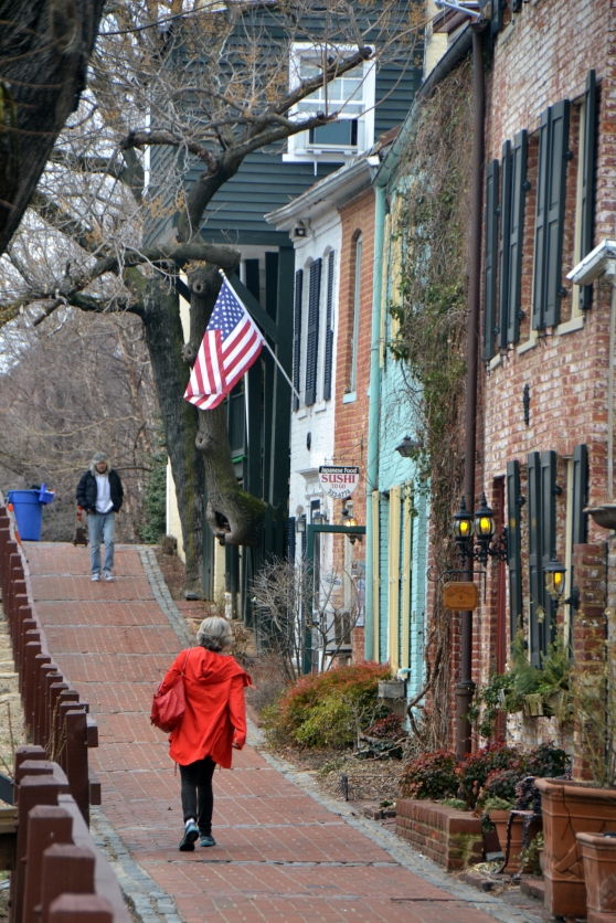 """Woman in Red"" • This is one of my favorite little streets to photography.  The building fronts, the American flag, the always-interesting people, and the canalside brick sidewalk are just too lovely to pass up."